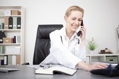 happy-physician-leaning-table-phone-adult-woman-white-medical-gown-her-talking-to-someone-over-53091406